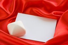 Jewerly  box and empty card. White jewerly  box and empty card on red satin Royalty Free Stock Photo