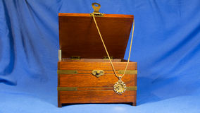 Jewerly pendant that was made using gold sovereign coin on wooden present box Stock Image