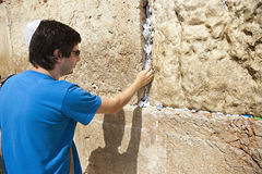 Placing a Note in the Wailing Wall. A Jewish adult (early 30's) caucasian man concentrated in prayer in front of the wailing wall in the old city of Jerusalem Stock Image