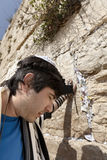 Jewish Man Praying at the Western Wall. A Jewish adult (early 30's) Caucasian man wearing a Jewish praying shawl, Yarmulke and Phylacteries on his head and left Stock Photography