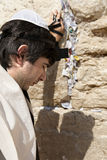 Jewish Man Praying at the Western Wall. A Jewish adult (early 30's) Caucasian man wearing a Jewish praying shawl, Yarmulke and Phylacteries on his head and left Royalty Free Stock Photos