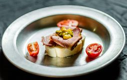 Jewish appetizer sandwich with pastrami, mustard relish, and cherry tomatoes. Jewish appetizer sandwich with pastrami, mustard relish and cherry tomatoes royalty free stock images