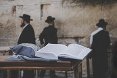 Jewish bible - Torrah on table on blurred background of praying Jews and wailing western wall. Israel. Jerusalem. Jewish bible - Torrah open on table on blurred royalty free stock photography