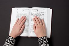 Jewish book, with woman`s hand, on black background. Text of the Hebrew, prayer. Woman prays with book. Jewish book, with woman`s hand, on black background Royalty Free Stock Image