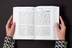 Jewish book, with woman`s hand, on black background. Text of the Hebrew, prayer. Woman reading book. Jewish book, with woman`s hand, on black background. Text Royalty Free Stock Image