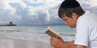 Prayer by the Sea. Jewish boy reads his torah with a beach scene in the background Royalty Free Stock Image