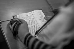 Jewish boy with Tefillin on his hand reading Torah at Bar Mitzvah. Jewish boy reading from Torah book with Tefillin on hand in israeli bar mitzvah holiday Royalty Free Stock Photos