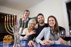 Jewish family celebrating Chanukah. At table with menorah stock photography