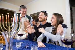 Jewish family celebrating Chanukah. At table with menorah royalty free stock image