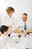 Jewish family celebrating passover. Mother serving Kneidel soup at Passover family Seder Stock Photography