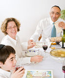Jewish family celebrating passover. Mother serving Kneidel soup at Passover family Seder Stock Images
