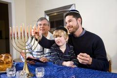 Jewish family lighting Chanukah menorah. Three generation Jewish family lighting Chanukah menorah stock photos