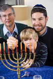 Jewish family lighting Chanukah menorah Royalty Free Stock Photos