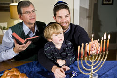 Jewish family lighting Hanukkah menorah. Four year old boy with grandfather and father lighting Hanukkah menorah royalty free stock photo