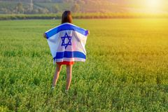 Jewish girl with flag of Israel on amazing landscape in beautiful summer. Back view Young woman patriot jewish girl standing with flag of Israel on amazing royalty free stock photography