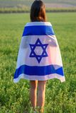 Jewish girl with flag of Israel on amazing landscape in beautiful summer. Back view Young woman patriot jewish girl standing with flag of Israel on amazing royalty free stock image