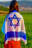 Jewish girl with flag of Israel on amazing landscape in beautiful summer. Back view Young woman patriot jewish girl standing with flag of Israel on amazing stock photo