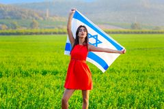 Jewish girl with flag of Israel on amazing landscape in beautiful summer. Young woman patriot jewish proud girl standing with flag of Israel on amazing stock photography