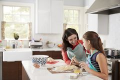 Jewish girl glazing plaited challah bread dough with her mum stock images