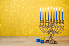 Jewish Hanukkah background with vintage menorah and spinning top dreidel over lights bokeh Stock Images