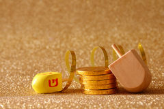 Jewish Hanukkah with dreidel (spinning top) and chocolate coins. Image of jewish holiday Hanukkah with wooden dreidel (spinning top) and chocolate coins on the Stock Photo