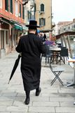 Jewish Hasidic Man with an umbrella walking in the street in the Jewish Quarter royalty free stock images