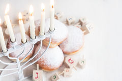 Jewish holiday Hannukah background. Jewish traditional holiday Hannukah with menorah, doughnuts and dreidles. Copy paste background stock images