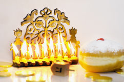 Jewish Holiday Hanukkah. Photo of a dreidel (spinning top), gelts (candy coins) and an ancient brass menorah for the Jewish holiday of Hanukkah Stock Images
