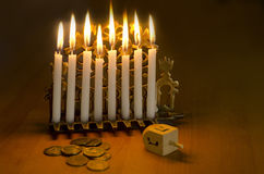 Jewish Holiday Hanukkah. Photo of a dreidel (spinning top), gelts (candy coins) and an ancient brass menorah for the Jewish holiday of Hanukkah