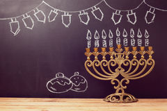 Jewish holiday Hanukkah background with menorah over chalkboard with hand sketched symbols royalty free stock image