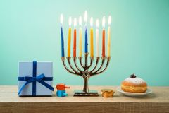 Jewish holiday Hanukkah background with menorah, sufganiyot, gif. T box and spinning top on wooden table