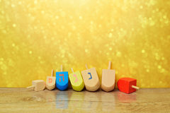 Jewish holiday Hanukkah background with spinning top dreidel over gold bokeh. Copy space for text Royalty Free Stock Photo