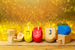 Jewish holiday Hanukkah background with spinning top dreidel on wooden table over golden bokeh Stock Images