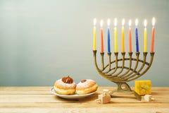 Jewish holiday Hanukkah background with sufganiyot and menorah o stock image