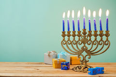 Jewish holiday Hanukkah background with vintage menorah and gift boxes. On wooden table Royalty Free Stock Photos