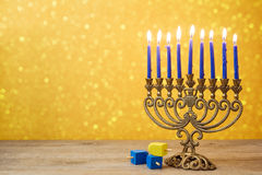 Jewish holiday Hanukkah background with vintage menorah and spinning top dreidel over lights bokeh. stock photos