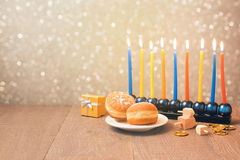 Jewish holiday Hanukkah celebration with menorah over bokeh background. Retro filter effect. Jewish Hanukkah holiday celebration with menorah over bokeh Royalty Free Stock Photography