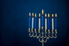 Jewish holiday of Hanukkah, hanukkah menorah. The Hanukkah menorah, traditional candle holder for nine candles for Jewish holiday of Hanukkah on dark blue Stock Image