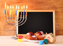 Jewish holiday Hanukkah with menorah, doughnuts over wooden table Stock Images