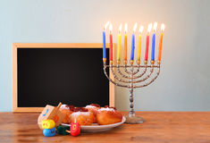 Jewish holiday Hanukkah with menorah, doughnuts over wooden table. Stock Photo