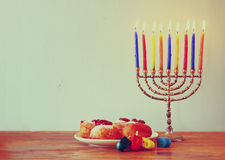 Jewish holiday Hanukkah with menorah, doughnuts over wooden table. retro filtered image Stock Image