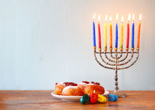 Jewish holiday Hanukkah with menorah, doughnuts over wooden table. retro filtered image.  Royalty Free Stock Image