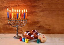 Jewish holiday Hanukkah with menorah, doughnuts over wooden table. retro filtered image Stock Photo