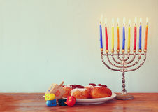 Jewish holiday Hanukkah with menorah, doughnuts over wooden table. retro filtered image. Royalty Free Stock Images