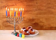 Jewish holiday Hanukkah with menorah, doughnuts over wooden table. retro filtered image. Royalty Free Stock Photos