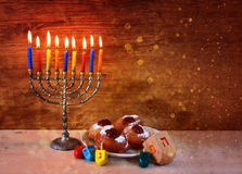 Jewish holiday Hanukkah with menorah, doughnuts over wooden table. retro filtered image