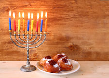 Jewish holiday Hanukkah with menorah, doughnuts over wooden table. retro filtered image. Stock Photography