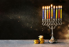 Jewish holiday Hanukkah with menorah. Low key image of jewish holiday Hanukkah with menorah (traditional Candelabra) and wooden dreidels (spinning top royalty free stock image