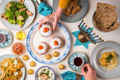 Jewish holiday Hanukkah, traditional feast, hands above table top view. Horizontal stock photos