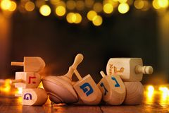 jewish holiday Hanukkah with wooden dreidels colection & x28;spinning top& x29; and gold garland lights on the table royalty free stock image
